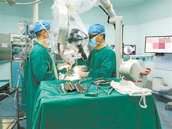 医生为患者进行显微镜下腰椎间盘微创手术。