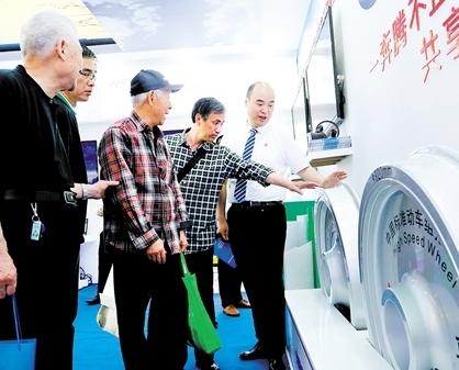 工作人员(右)在首届品博会安徽马钢展台向观众介绍中国标准动车组拖车轮实物展品。新华社