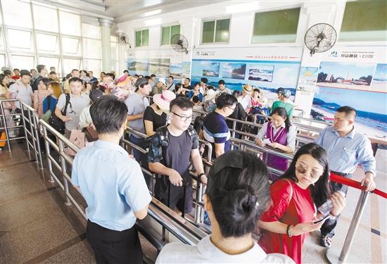 在山咀码头,游客们有秩序地排队验票登船。