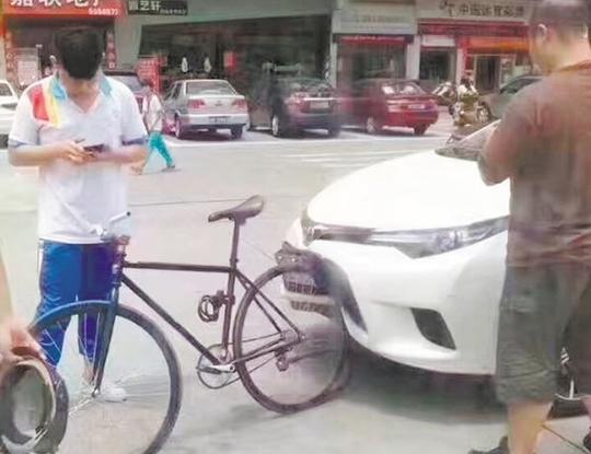 日系车追尾自行车后,轿车车头严重变形,而自行车只是车胎脱落。微信朋友圈截图