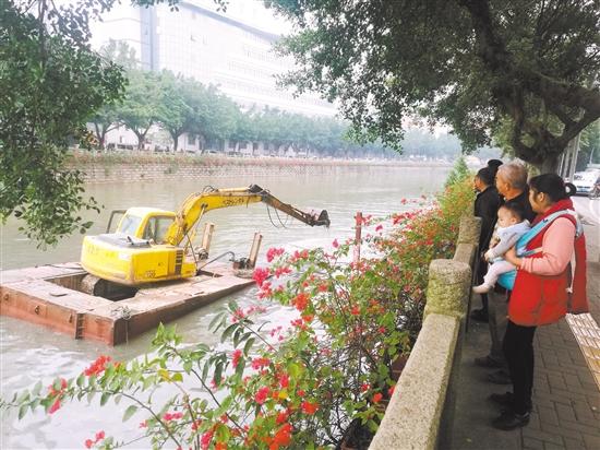 挖掘机下河清淤吸引不少市民围观。