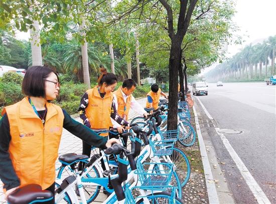 江门移动志愿者在整理路旁的共享单车。