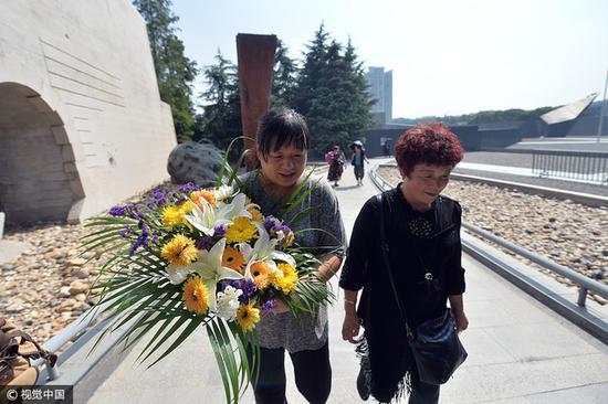 南京大屠杀遇难者彭玉珍家属献上鲜花。 图片来源:视觉中国