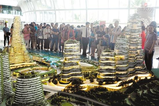 众多来自中国的看房客在碧桂园森林城市看项目沙盘。